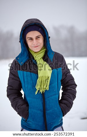 Closeup portrait of a cheerful teenager boy standing on a snowy field with forest on background - stock photo