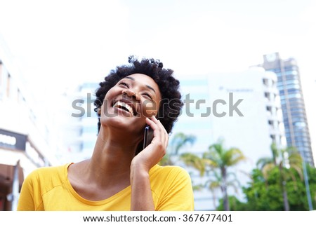 Closeup portrait of a cheerful young woman talking on mobile phone outdoors in the city   - stock photo