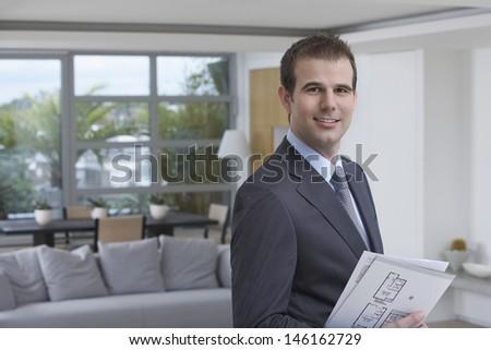 Closeup portrait of a confident male estate agent smiling - stock photo