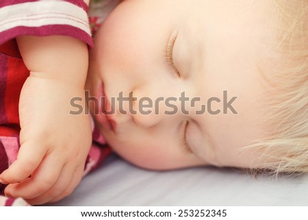 Closeup portrait of a cute adorable white blond Caucasian baby child toddler sleeping dreaming, lying on a bed, indoor - stock photo