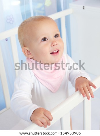 Closeup portrait of a cute baby smiling in white crib