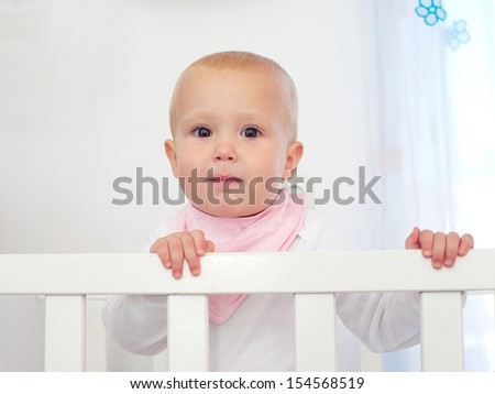 Closeup portrait of a cute baby standing in white cot