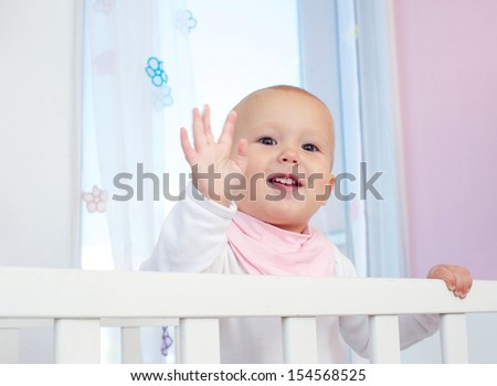 Closeup portrait of a cute baby waving hello with hand