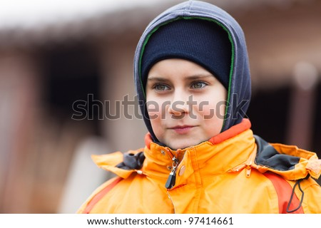 Closeup portrait of a cute boy with coat and hood outdoor - stock photo