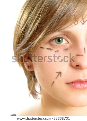 Closeup portrait of a cute Caucasian girl whose face is marked with lines and arrows for facial cosmetic surgery. Isolated on white. - stock photo
