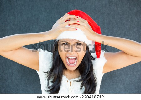 Closeup portrait of a cute Christmas woman with a red Santa Claus hat, white dress, hands on head, stressed out, yelling, showing frustration. Negative human emotions on isolated grey background.  - stock photo
