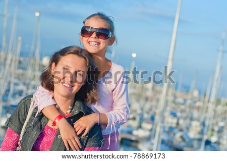Closeup Portrait of a cute girl with her mother in the background of yachts - stock photo