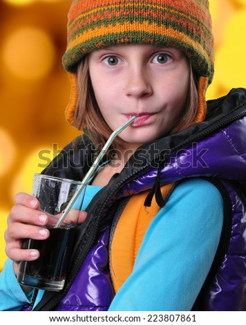 Closeup portrait of a cute girl with yellow backpack hat drinking cola through straw  - stock photo