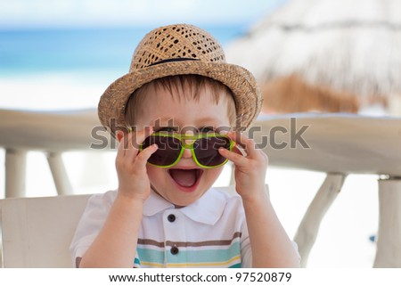 Closeup portrait of a cute happy toddler boy playing with sunglasses on a tropical beach - stock photo