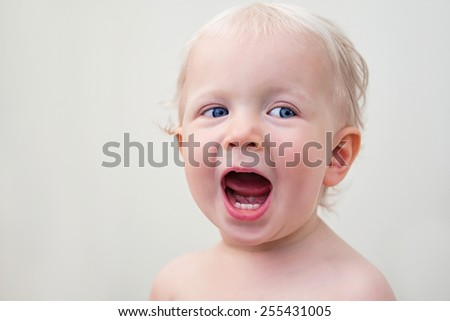 Closeup portrait of a cute laughing crying screaming  blond baby with blue eyes on a light background - stock photo