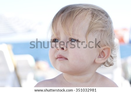 Closeup portrait of a cute one year old girl. Charming curly blonde toddler with blue eyes and perfect nose having rest on the beach. Attractive beautiful child. Summer time. Outdoors. Colorful photo. - stock photo