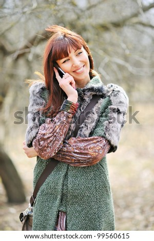 Closeup portrait of a cute young girl talking on mobile phone outdoors - stock photo