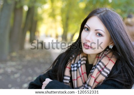 Closeup portrait of a cute young woman in autumn park - stock photo