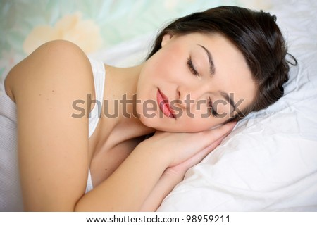 Closeup portrait of a cute young woman on the bed