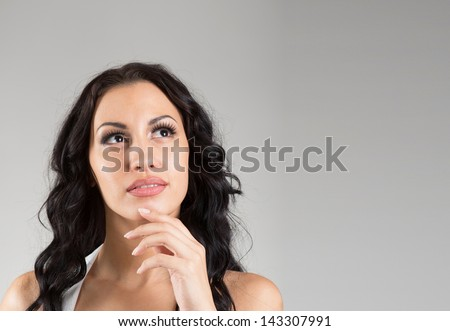 Closeup portrait of a dreaming brunette woman on gray background - stock photo