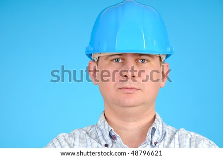 Closeup portrait of a engineer with blue hard hat on blue background - stock photo