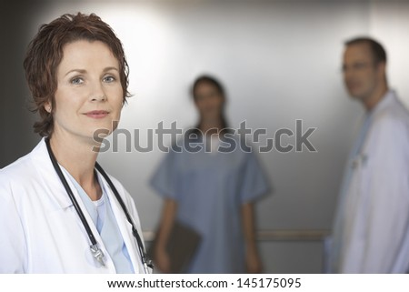 Closeup portrait of a female doctor with colleagues in elevator - stock photo