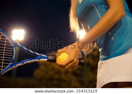 Closeup portrait of a female tennis player holding racket and ball - stock photo