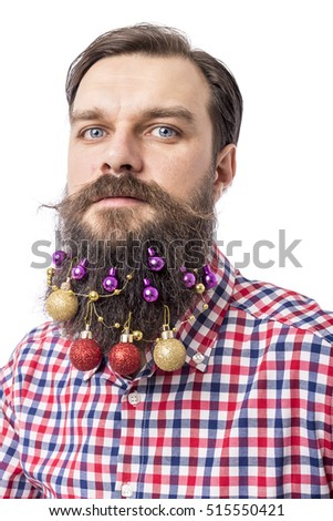 Closeup portrait of a funny man with decoration balls in his beard over white background