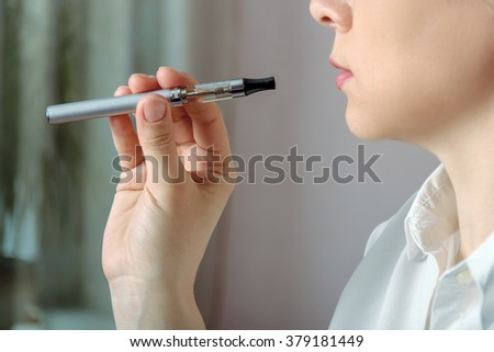 Closeup portrait of a girl with e-cigarette in his hand. Concept: safe way of smoking, how to stop smoking - stock photo