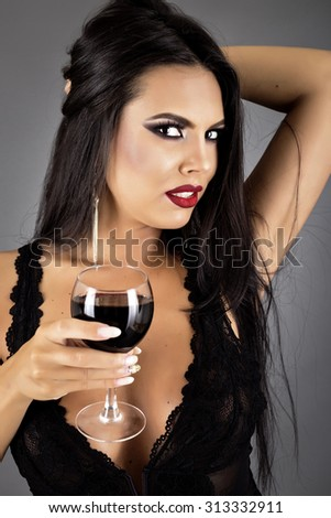 Closeup portrait of a gorgeous brunette young woman in sexy black lingerie holding a glass of wine isolated over gray background - stock photo