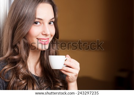 Closeup portrait of a gorgeous young brunette woman holding cup of coffee. - stock photo