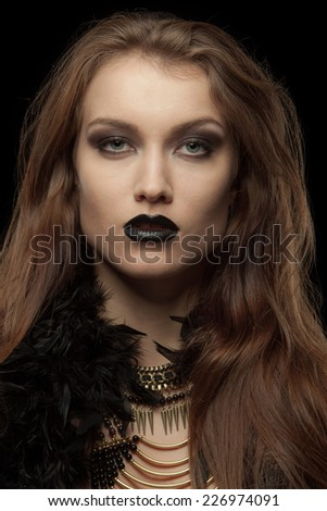 Closeup portrait of a gothic femme fatale with black lips on black background - stock photo