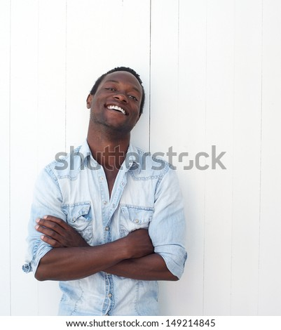 Closeup portrait of a handsome black man with arms crossed, leaning against white background - stock photo