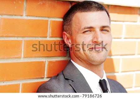 Closeup portrait of a handsome businessman against red brick wall - stock photo