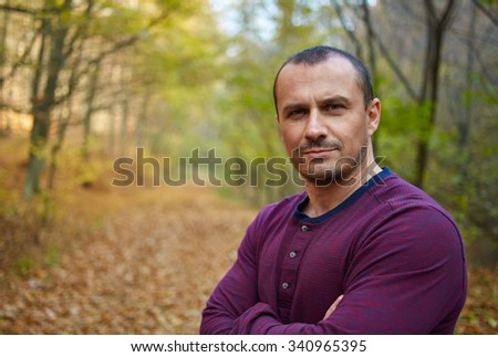 Closeup portrait of a handsome caucasian man in his forties outdoor in the forest - stock photo