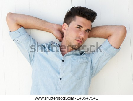 Closeup portrait of a handsome male fashion model with arms raised behind head - stock photo