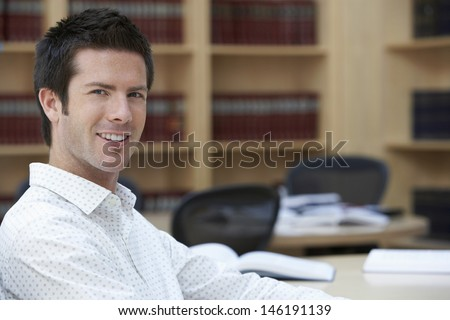 Closeup portrait of a handsome smiling office worker sitting in office - stock photo