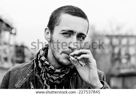 Closeup portrait of a handsome smoking young man. Black and white - stock photo