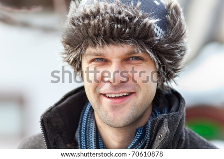 Closeup portrait of a handsome young caucasian man with cap outdoor - stock photo