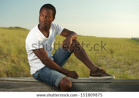 Closeup portrait of a handsome young man sitting alone outside - stock photo
