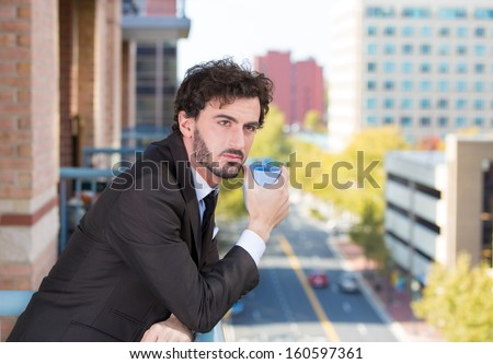 Closeup portrait of a handsome young man with a cup of coffee, enjoying life on outside balcony on background of trees and city buildings. Urban life style. Corporate life and success - stock photo