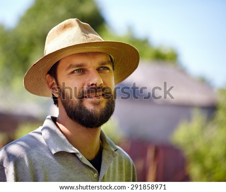 Closeup portrait of a hansome bearded young farmer outdoor - stock photo
