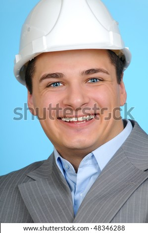 Closeup portrait of a happy engineer with white hard hat on blue background