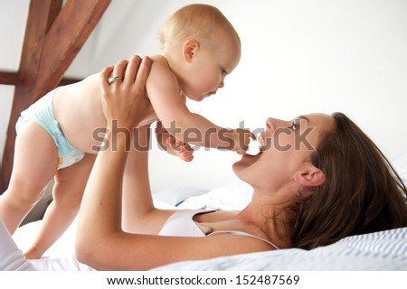 Closeup portrait of a happy mother and baby playing in bed - stock photo