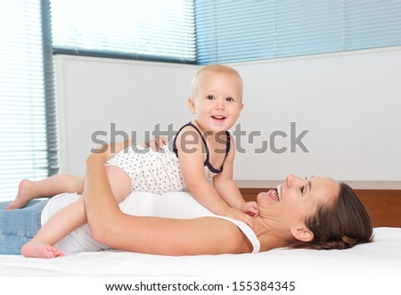Closeup portrait of a happy mother embracing cute baby in bed