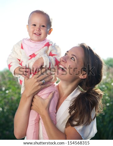 Closeup portrait of a happy mother holding cute baby outdoors - stock photo