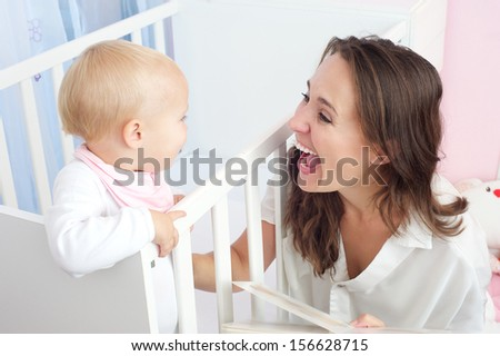 Closeup portrait of a happy mother laughing with cute baby in crib