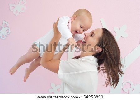 Closeup portrait of a happy mother playing with cute baby