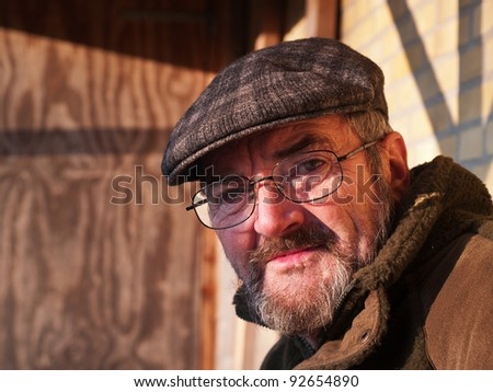 Closeup portrait of a happy smiling senior man with a hat outdoors - stock photo