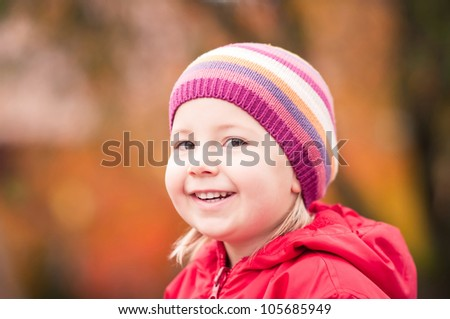 Closeup portrait of a happy toddler girl on autumn day - stock photo
