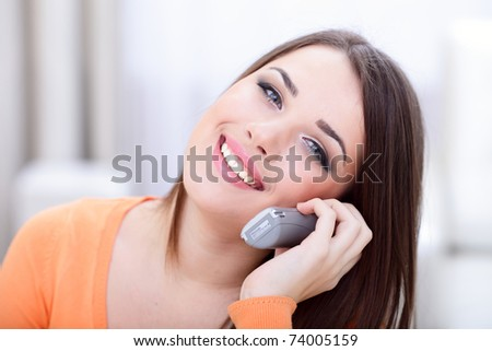 Closeup portrait of a happy woman on phone at home - stock photo