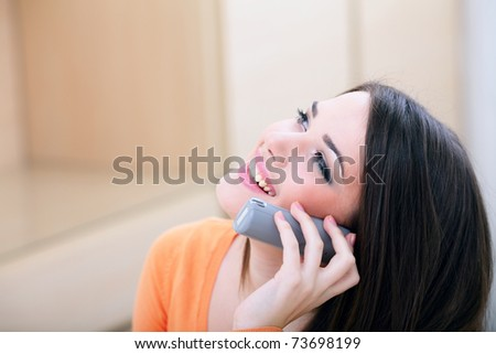 Closeup portrait of a happy woman on phone at home looking at copyspace