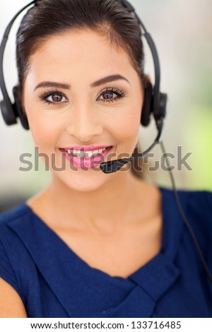 Closeup portrait of a happy young call centre employee smiling with a headset - stock photo