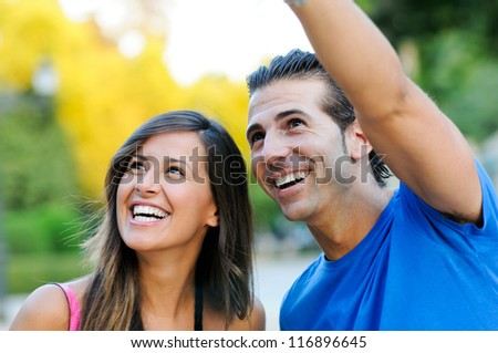 Closeup portrait of a happy young couple looking at something interesting - Copyspace - stock photo