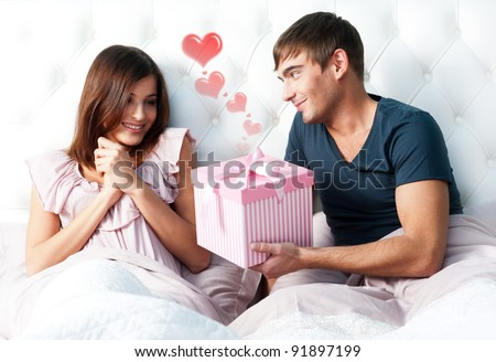 Closeup portrait of a happy young couple relaxing on the bed. Man making a gift to his girlfriend. Saint Valentine`s day concept. Graphic heart. - stock photo